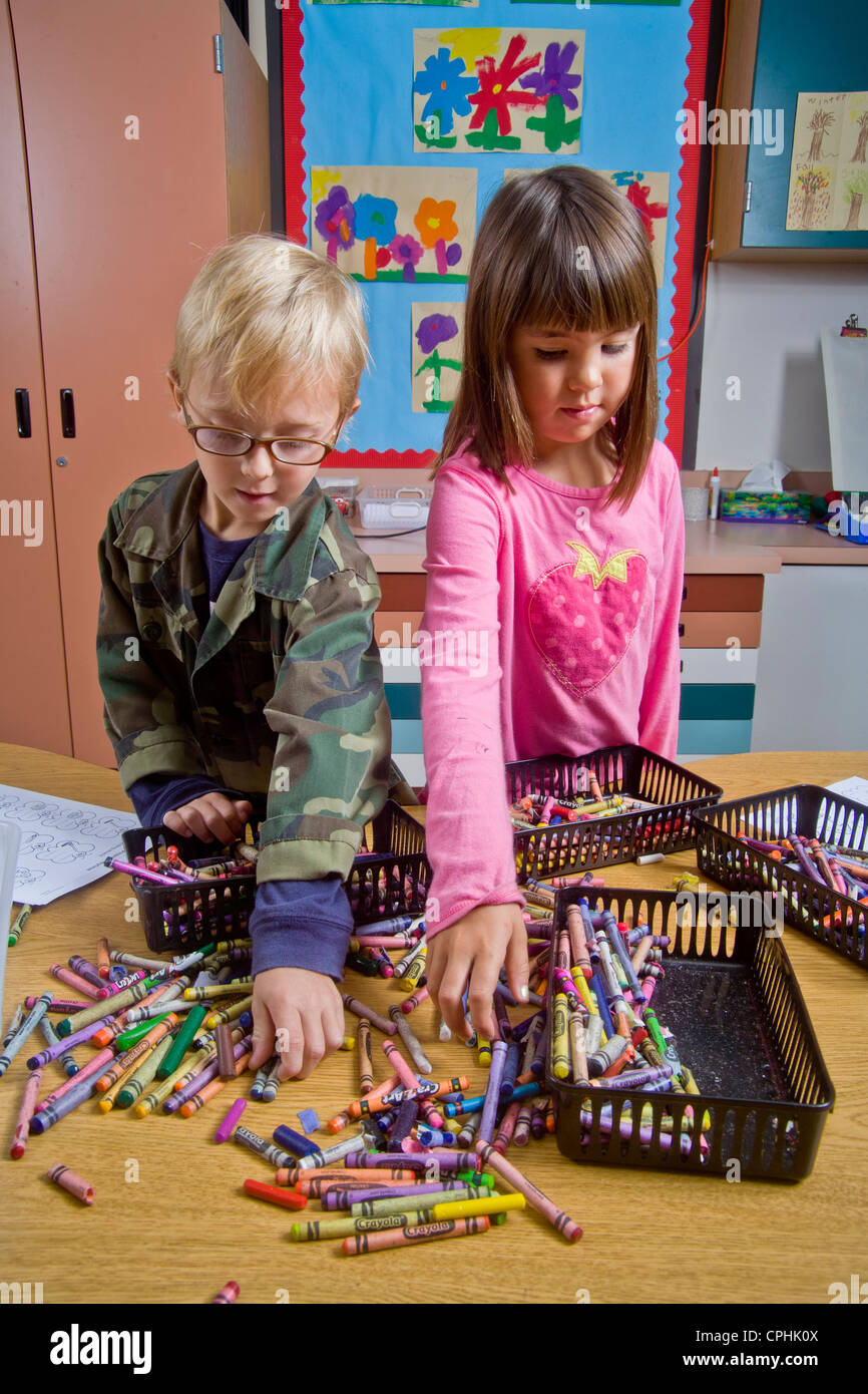 Kindergarten children in San Clemente CA collect and organize a table full of classroom objects including crayons - Stock Image