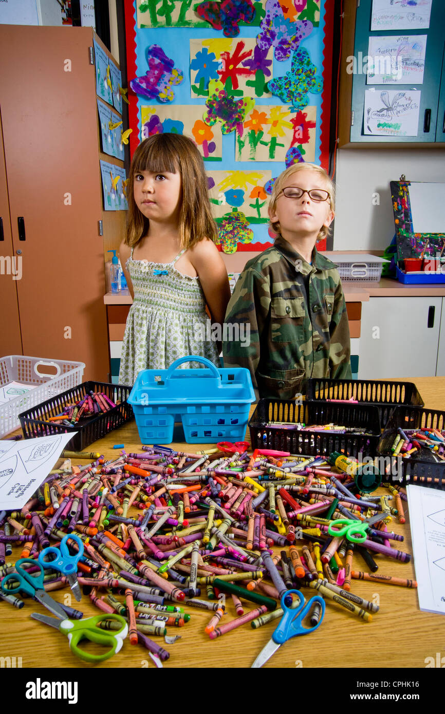 Kindergarten children in San Clemente CA contemplate a table full of classroom objects including crayons and worksheets - Stock Image