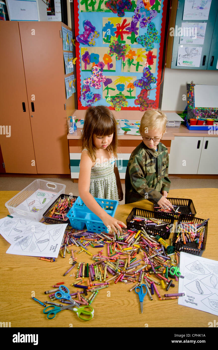Kindergarten children in San Clemente CA collect and organize a table full of classroom objects including crayons Stock Photo
