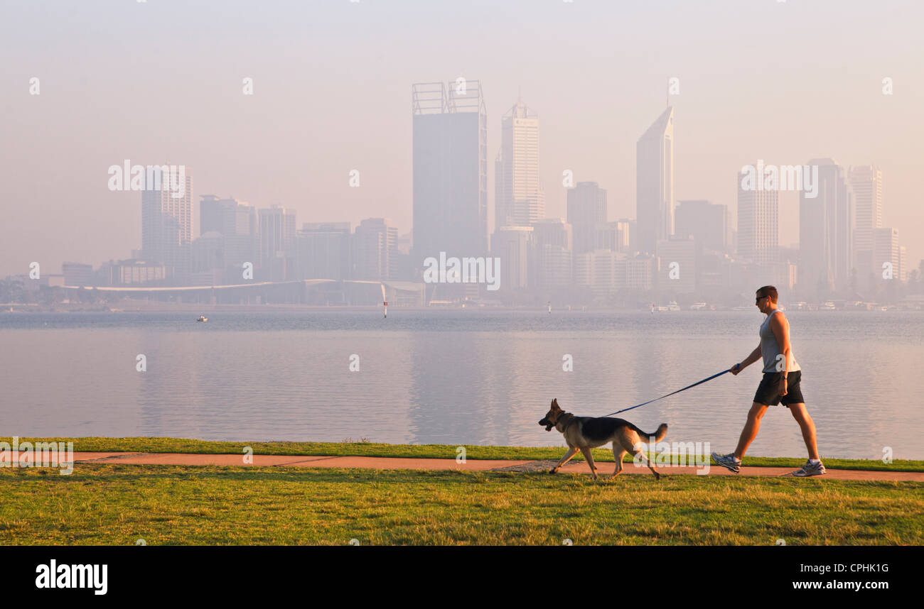 Man walking a dog down path beside river with the silhouette of a misty city skyline in the background. - Stock Image