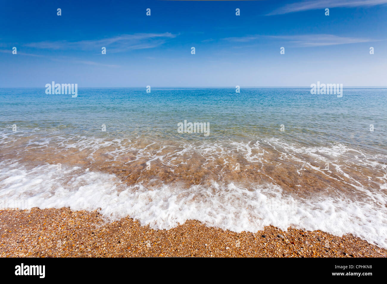 Glorious summers day with waves lapping the shore on a pebble beach. - Stock Image