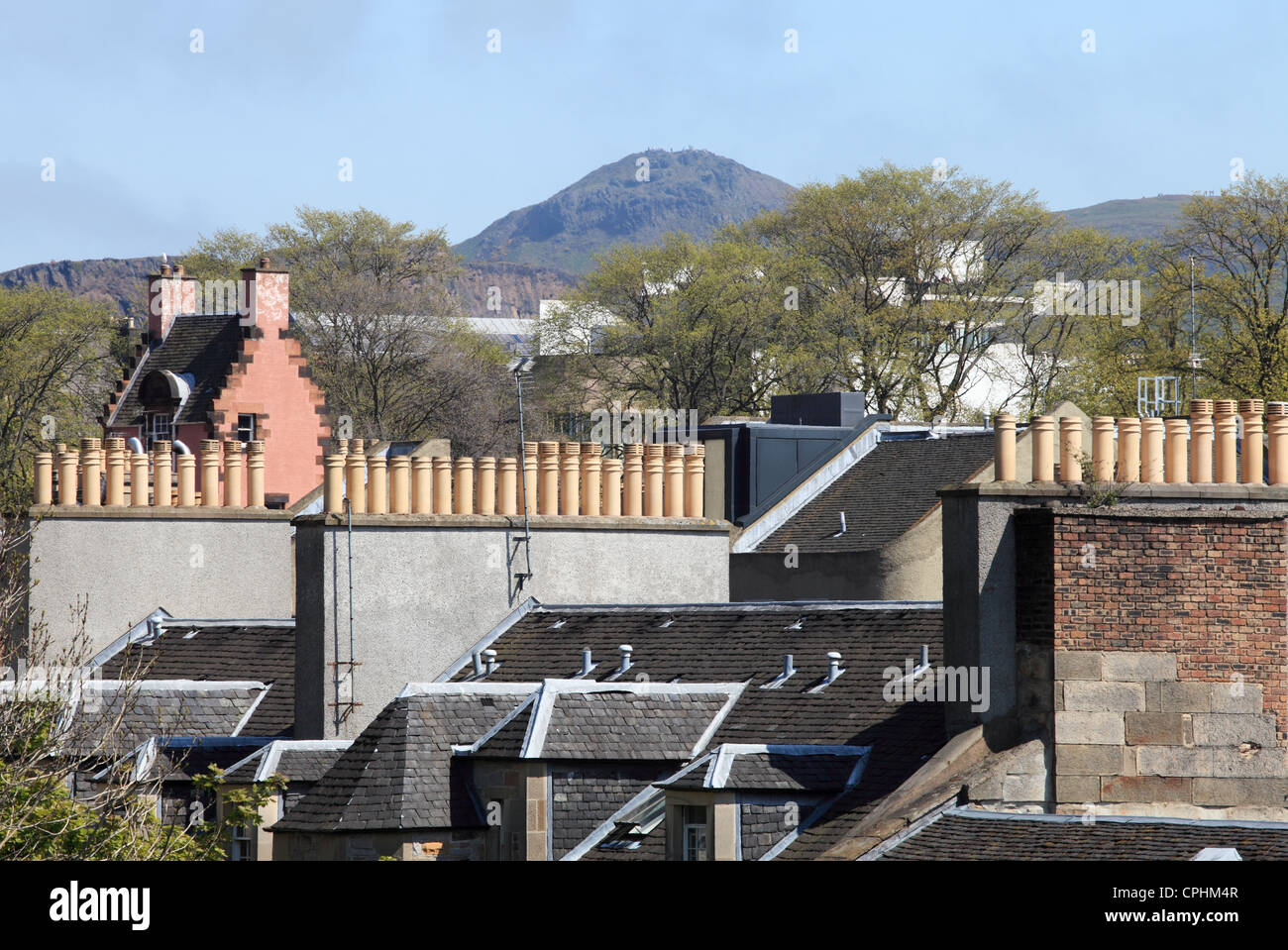 View of Arthur's Seat in the distance past rows of chimney pots within Edinburgh Scotland UK - Stock Image