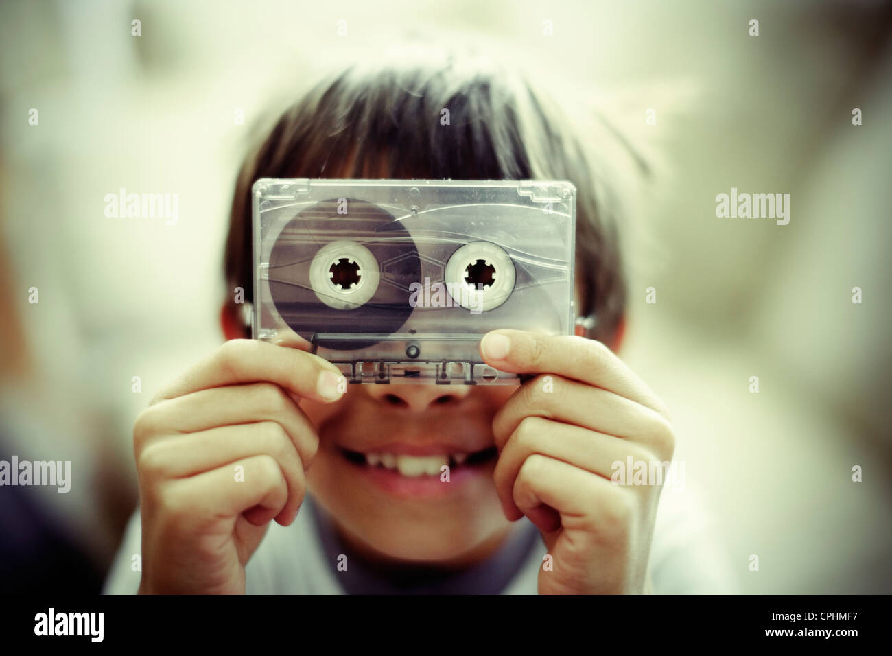 Boy holds old casette tape. - Stock Image