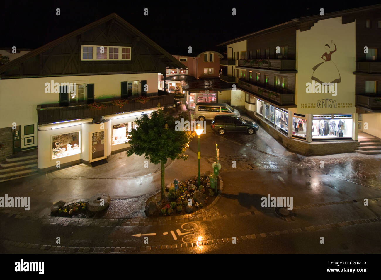 Nighttime view of Hauptstrasse, Mayrhofen with the wet cobbles illuminated by the shop windows - Stock Image