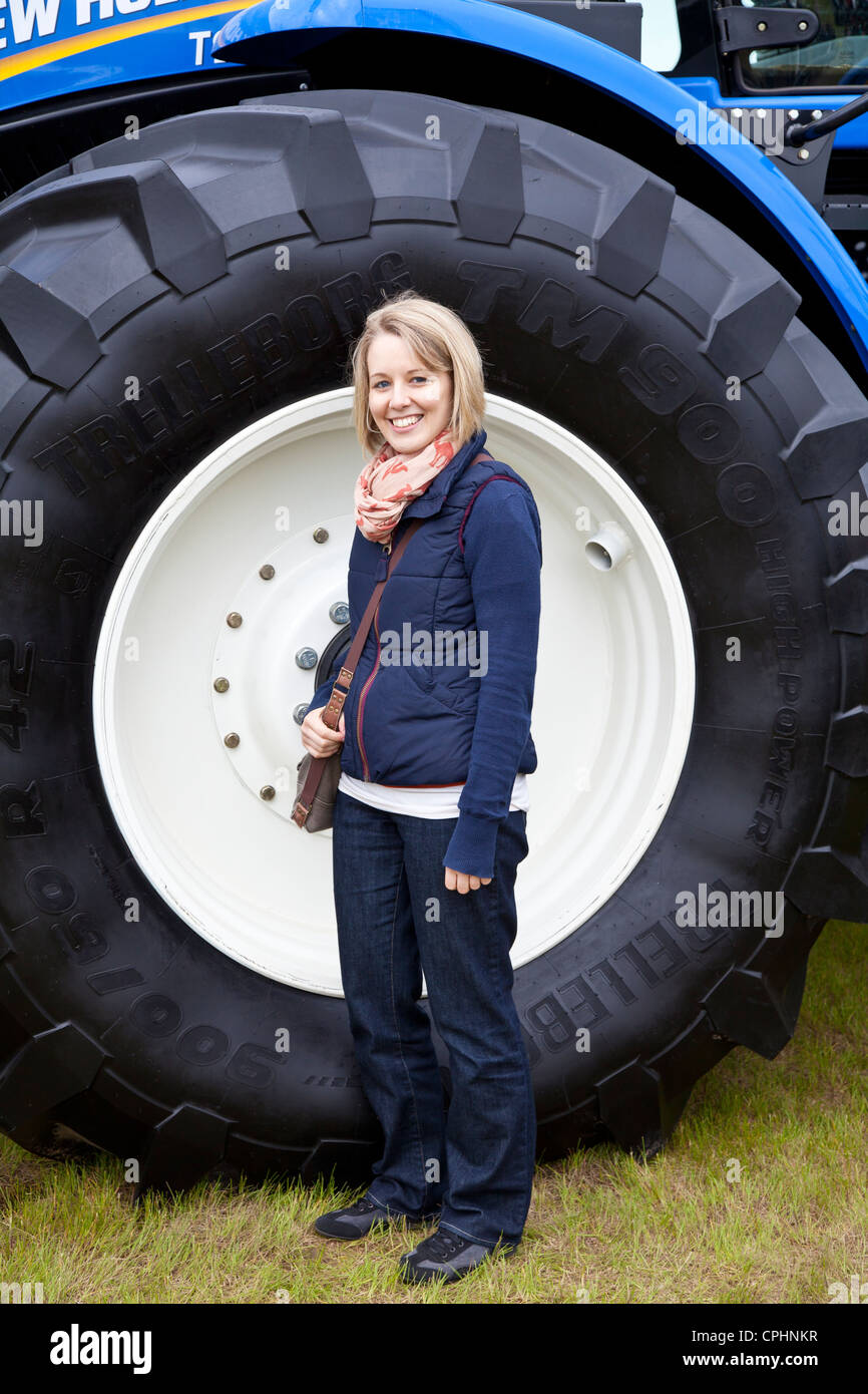 Large Tractor Wheels : Pretty girl standing next to large tractor wheel stock