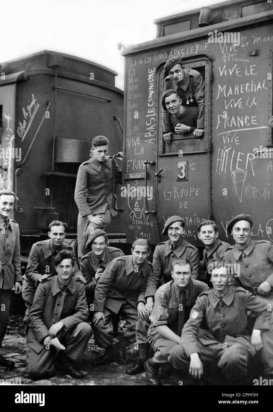 Members of the Legion of French Volunteers pose beside their train wagon, which is painted with anti-semitic and - Stock Image