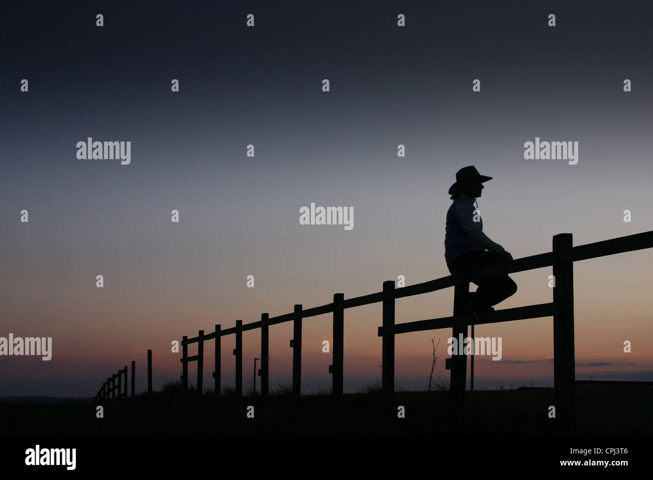 Cowgirl sitting on rail fence at sunset. - Stock Image
