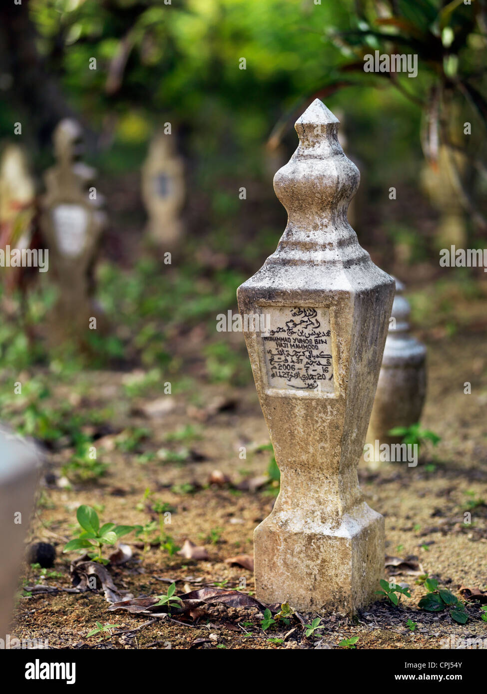 A grave marker in a cemetery located in the coastal town of Johor Lama. - Stock Image