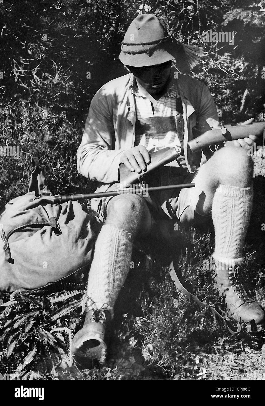 Poacher with carbine - Stock Image