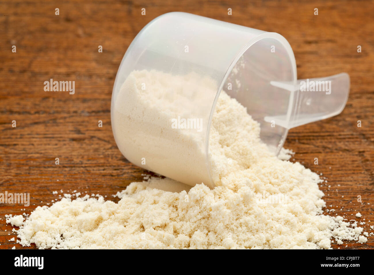 plastic measuring scoop of white powder (whey protein) against grunge wood background - Stock Image