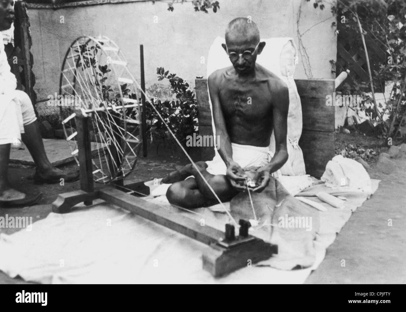Gandhi using a Spinning Wheel (b/w photo) - Stock Image