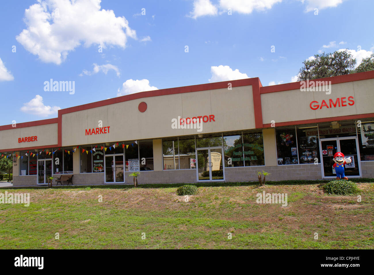 Clermont Florida barber market doctor games building businesses small town strip mall commercial building - Stock Image