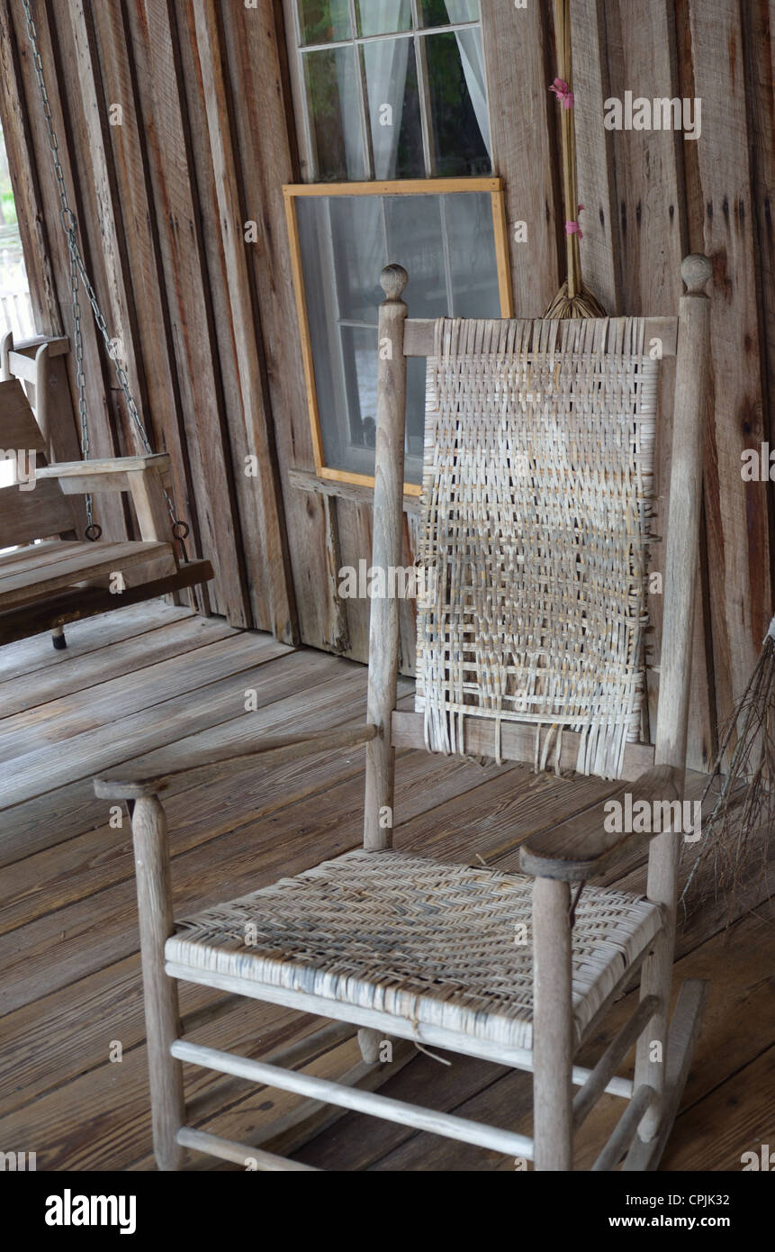 Antique rocking chair on a historical cabin's front porch - Stock Image