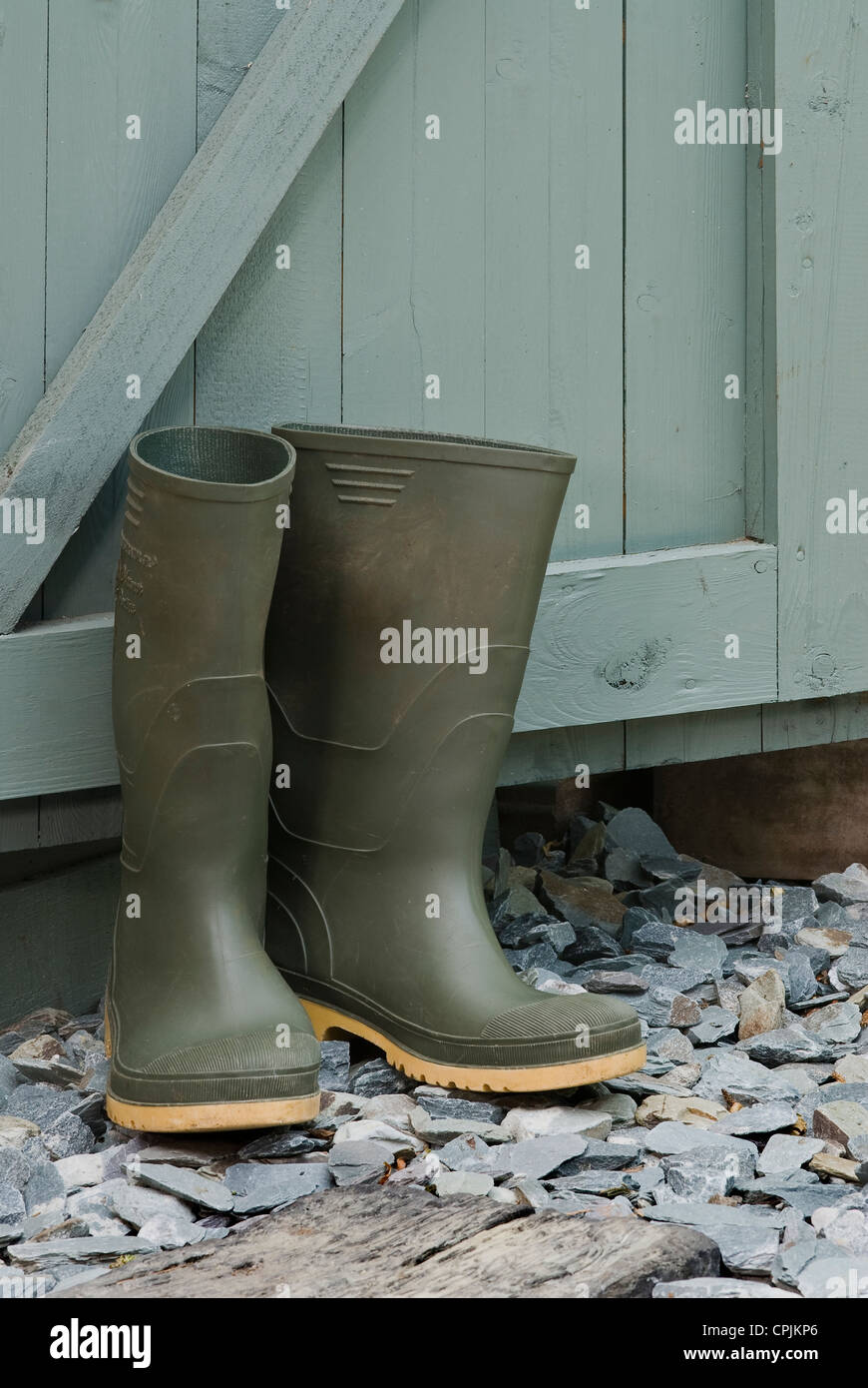 Pair of green wellington boots outside a garden shed. Stock Photo