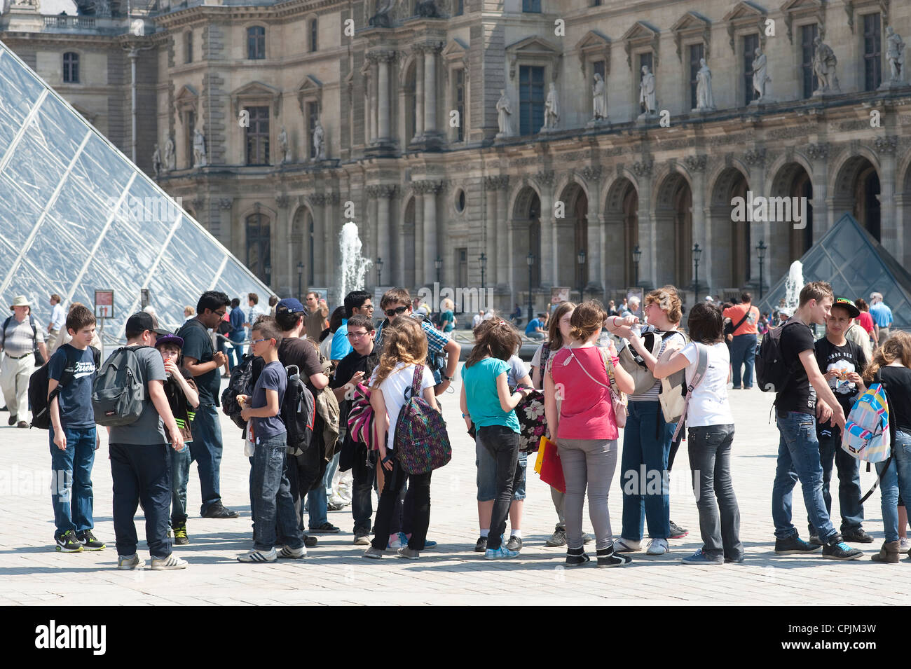 Paris, France -  A group of students visiting Paris in front of the Louvre Museum. - Stock Image