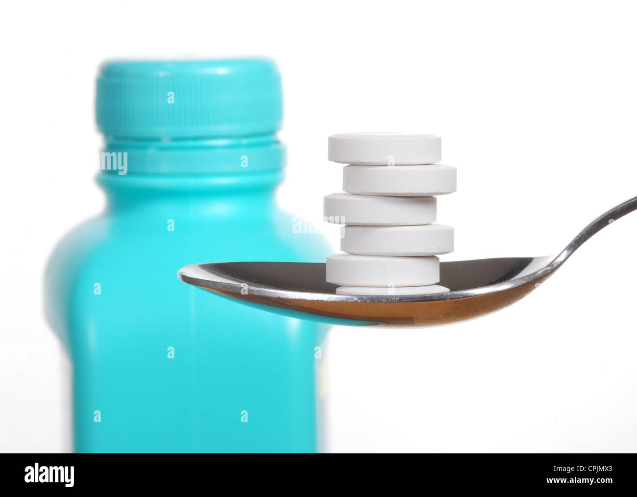 Antacid tablets on a spoon, a bottle of antacid blurred in the background - Stock Image