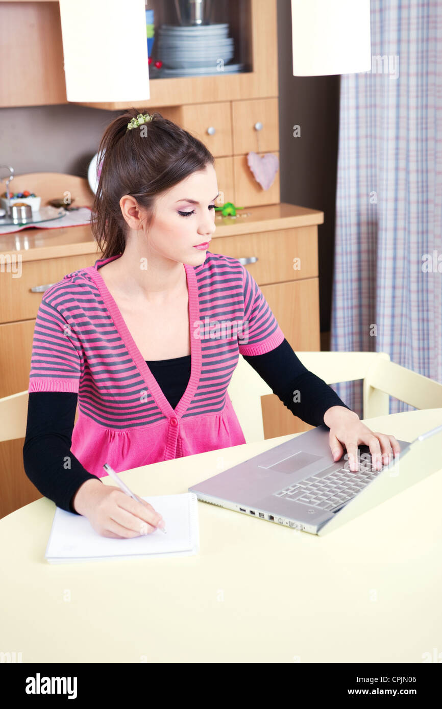 Pretty young girl working on laptop at home - Stock Image