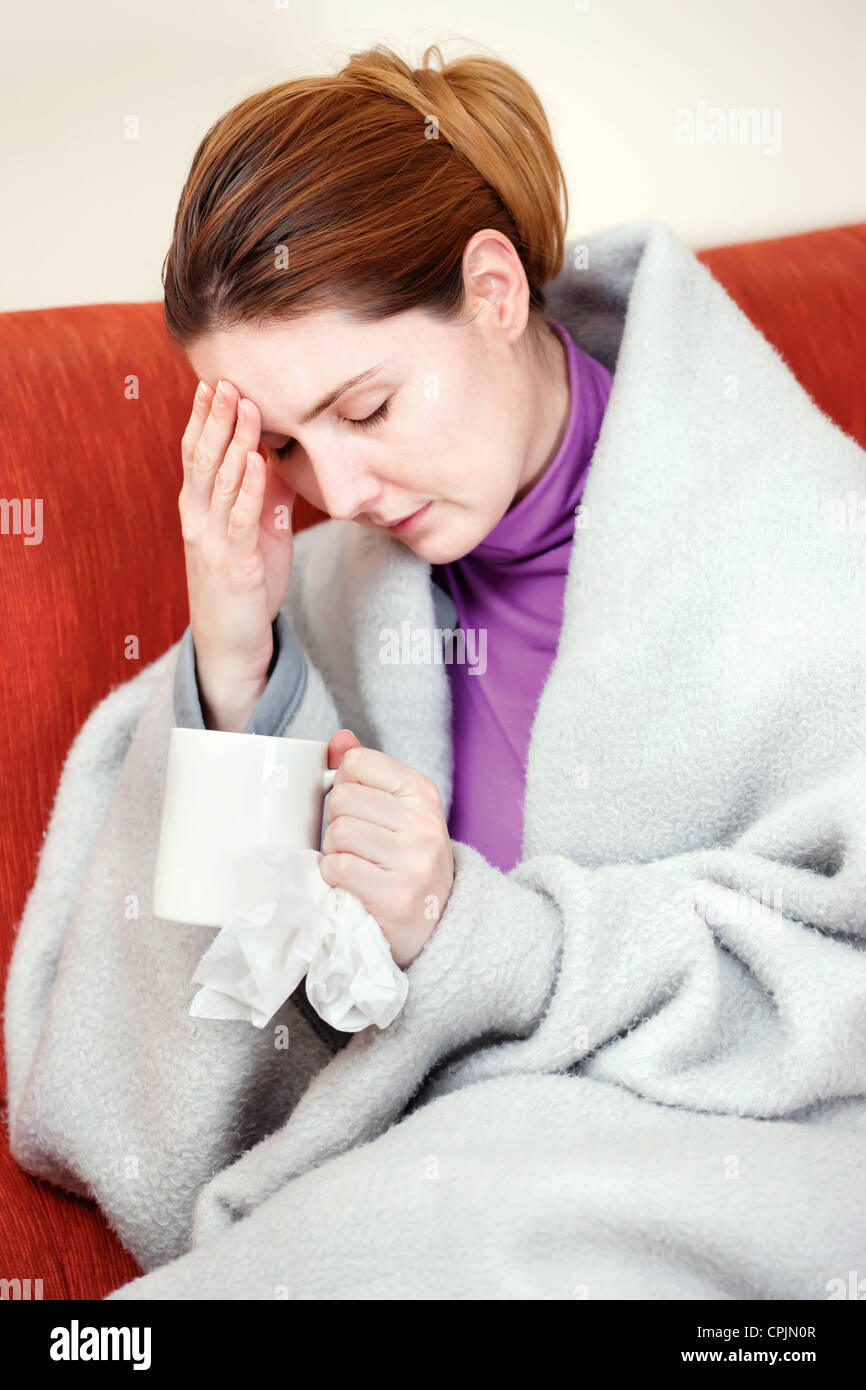 A young sick woman with a cup of tea in her hand. She hold her head in pain - Stock Image