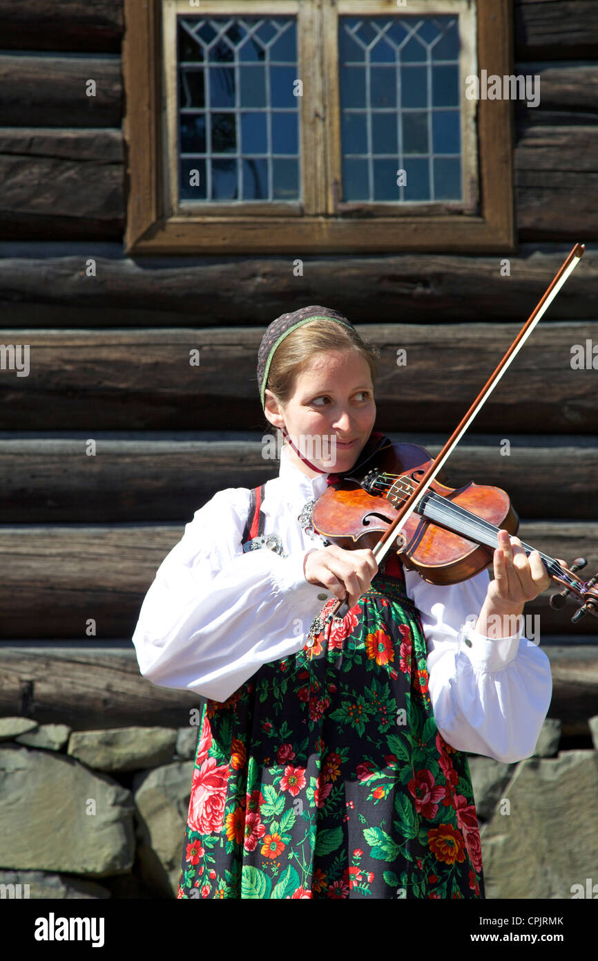 Norwegian female student playing violin in traditional dress, Norsk Folkemuseum Folk Museum, Bygdoy, Oslo, Norway, - Stock Image