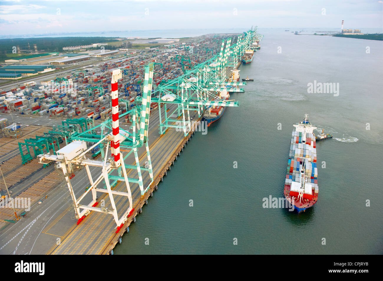A ship passing by a container terminal shipping port in Johor, Malaysia. - Stock Image
