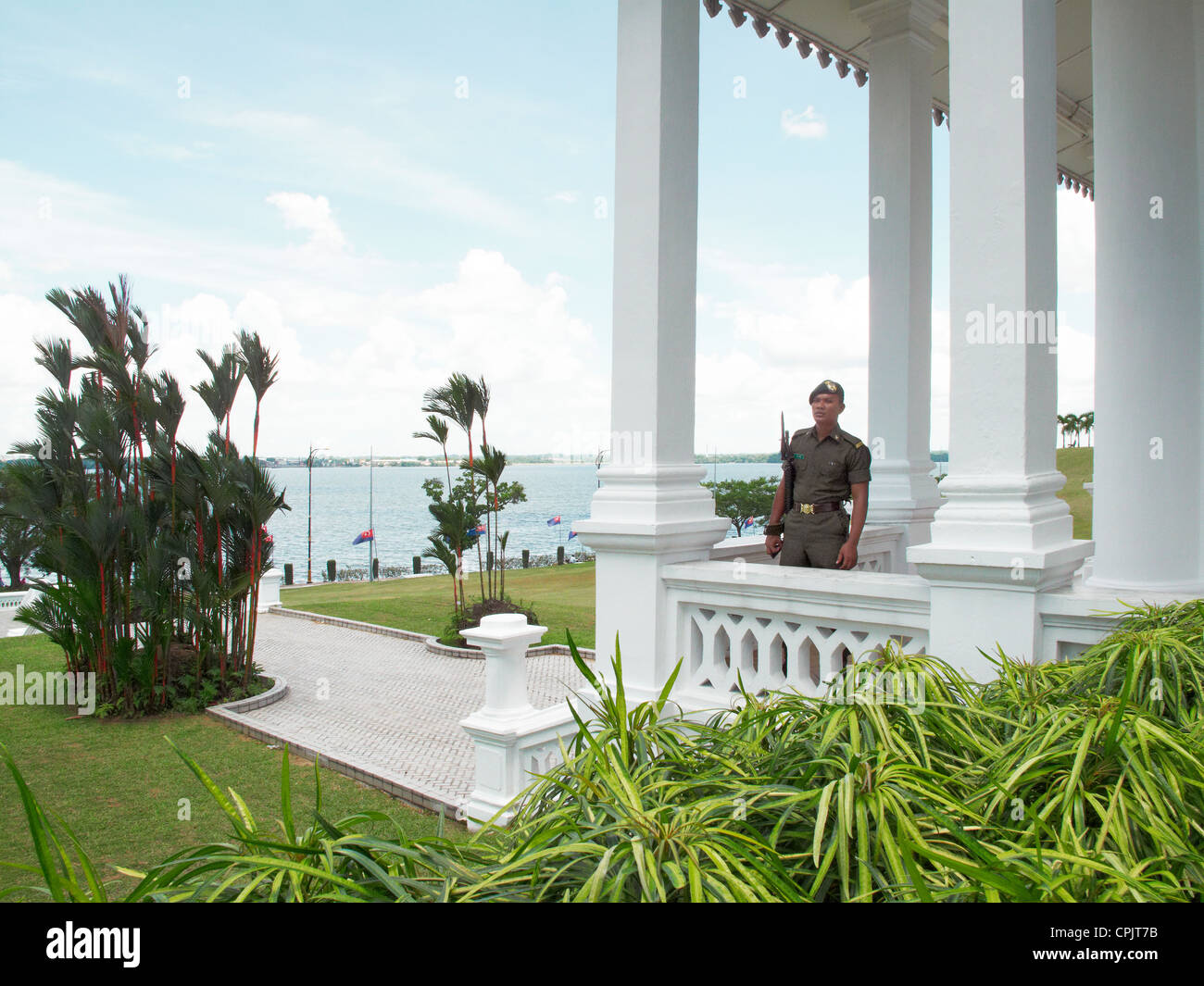 A security guard stands monitoring the courtyard at The Royal Sultan Abu Bakar Museum - Stock Image
