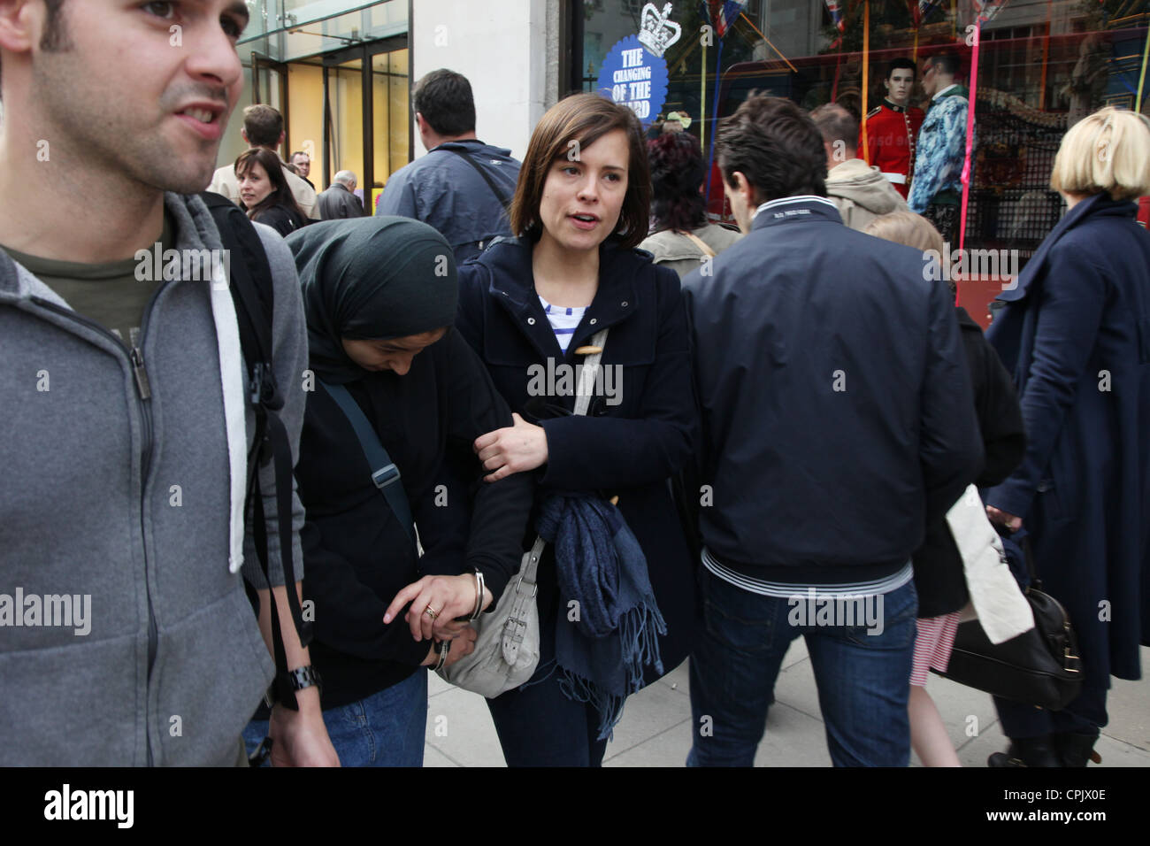 A woman is marched away by an undercover police officer to be arrested for begging in London's West End - Stock Image