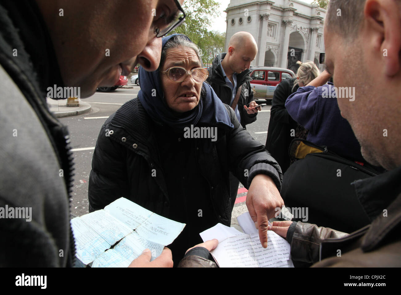 A woman's document's are checked by border control officials in London's West End. She was seen begging - Stock Image