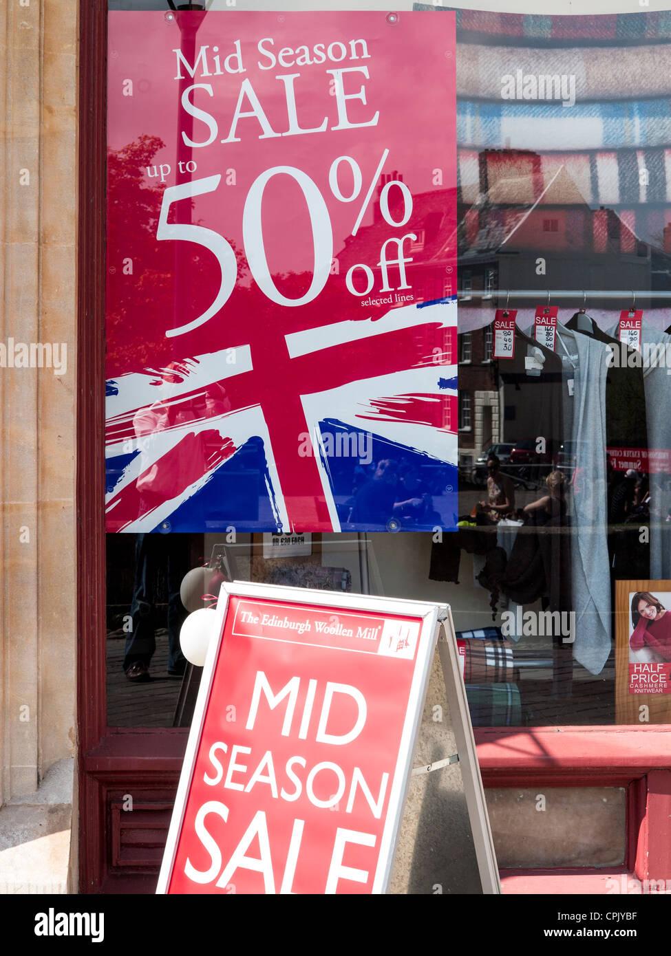a6810b8cbb0c9 50% off sale poster in Edinburgh Woolen Mill shop window in Exeter, Devon,