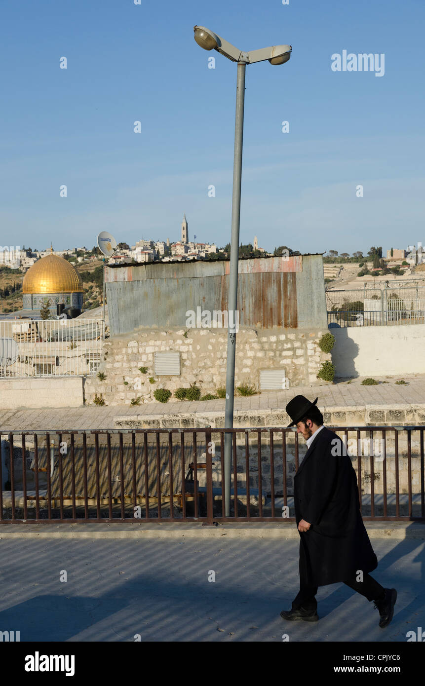 Orthodox jew walking with Dome of the Rock and lamppost in background. Jerusalem Old City. Israel. - Stock Image