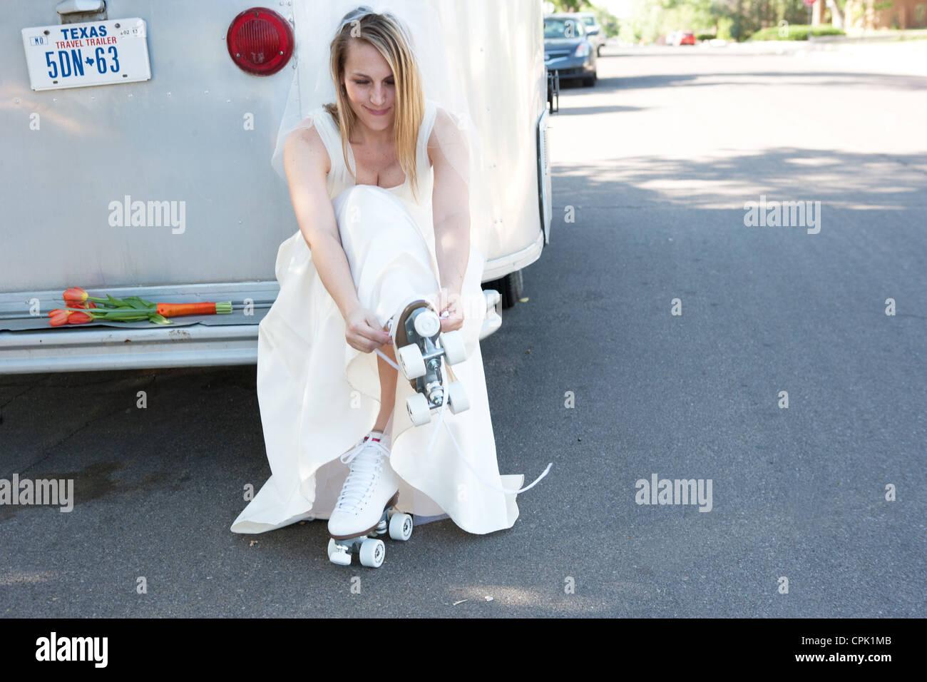 Bride putting on roller skates. - Stock Image