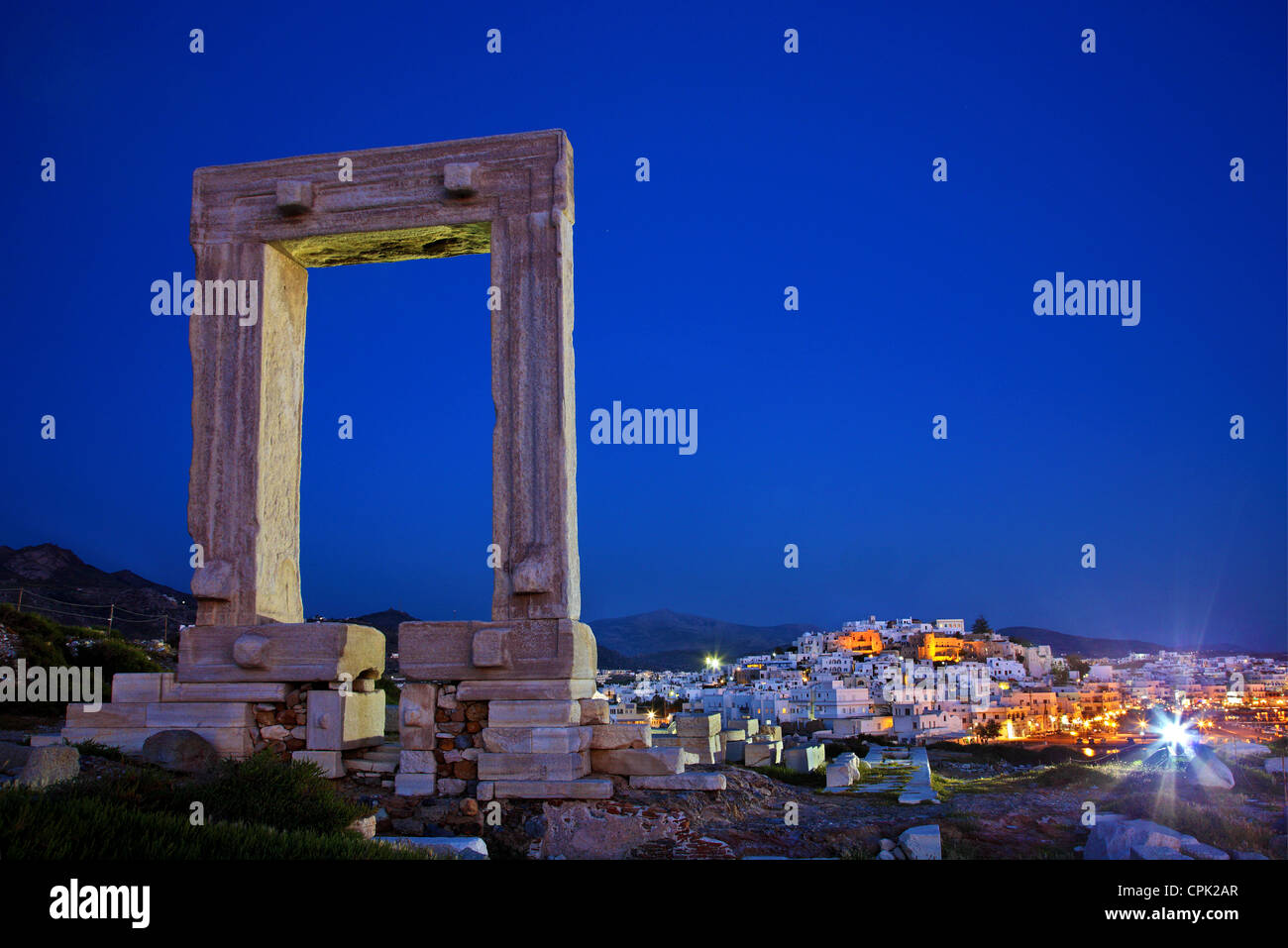 The Portara (temple of Apollo) and the Chora ('capital') of Naxos island in the background. Cyclades, Greece - Stock Image