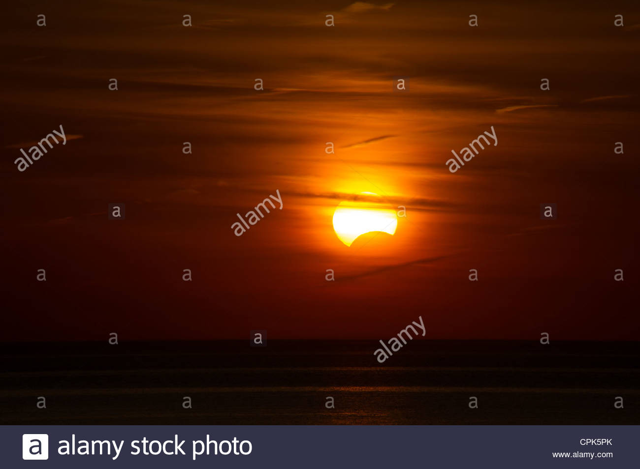 Partial Solar Eclipse at sunset in Ontario Canada on Lake Huron - Stock Image