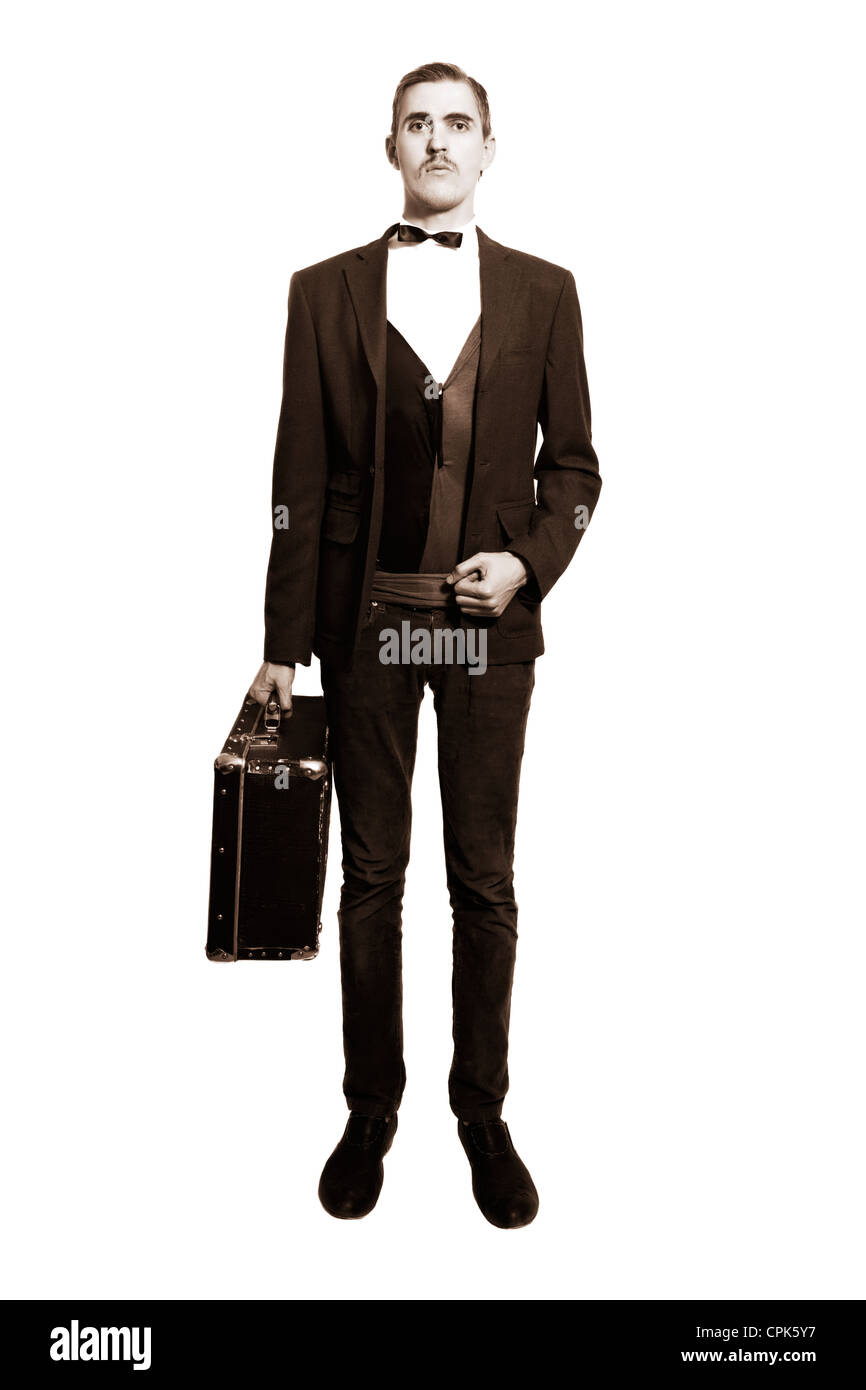 Retro portrait of a young man standing on a white background, with a suitcase isolated on white background Stock Photo