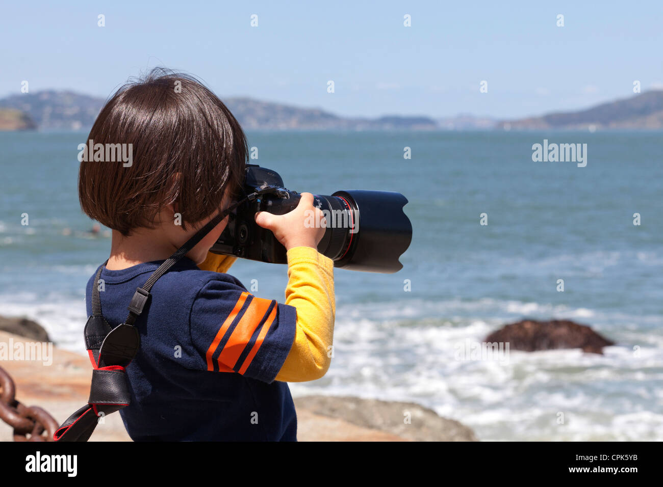 Child photographer taking pictures with dSLR camera - USA - Stock Image