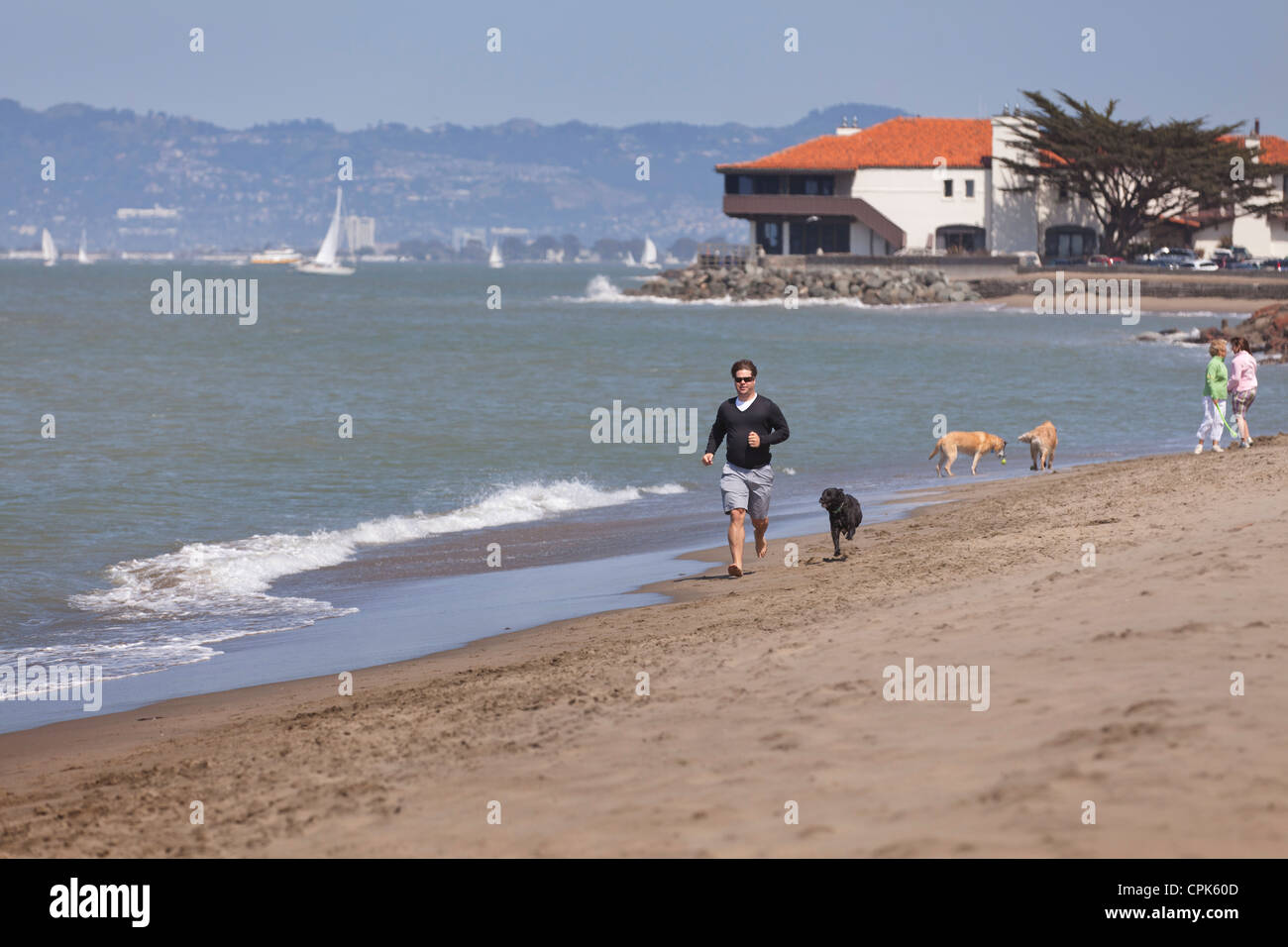 A man running on the beach with a dog Stock Photo
