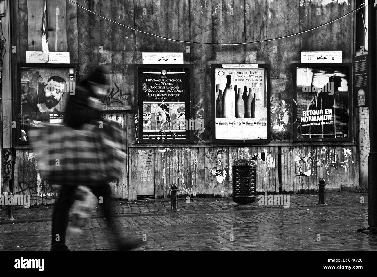 Scenes of Brussels downtown, people passing a wall with adverts. Shot at low shutter speed - Stock Image