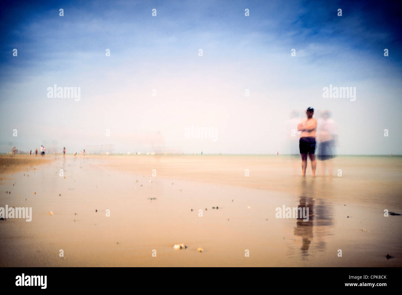 People on the beach, Sanlucar de Barrameda, Spain. Daylight long exposure shot by the use of neutral density filters. - Stock Image