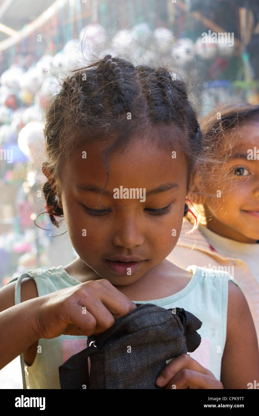 young girl looking inside purse, market, Antsirabe, Madagascar - Stock Image