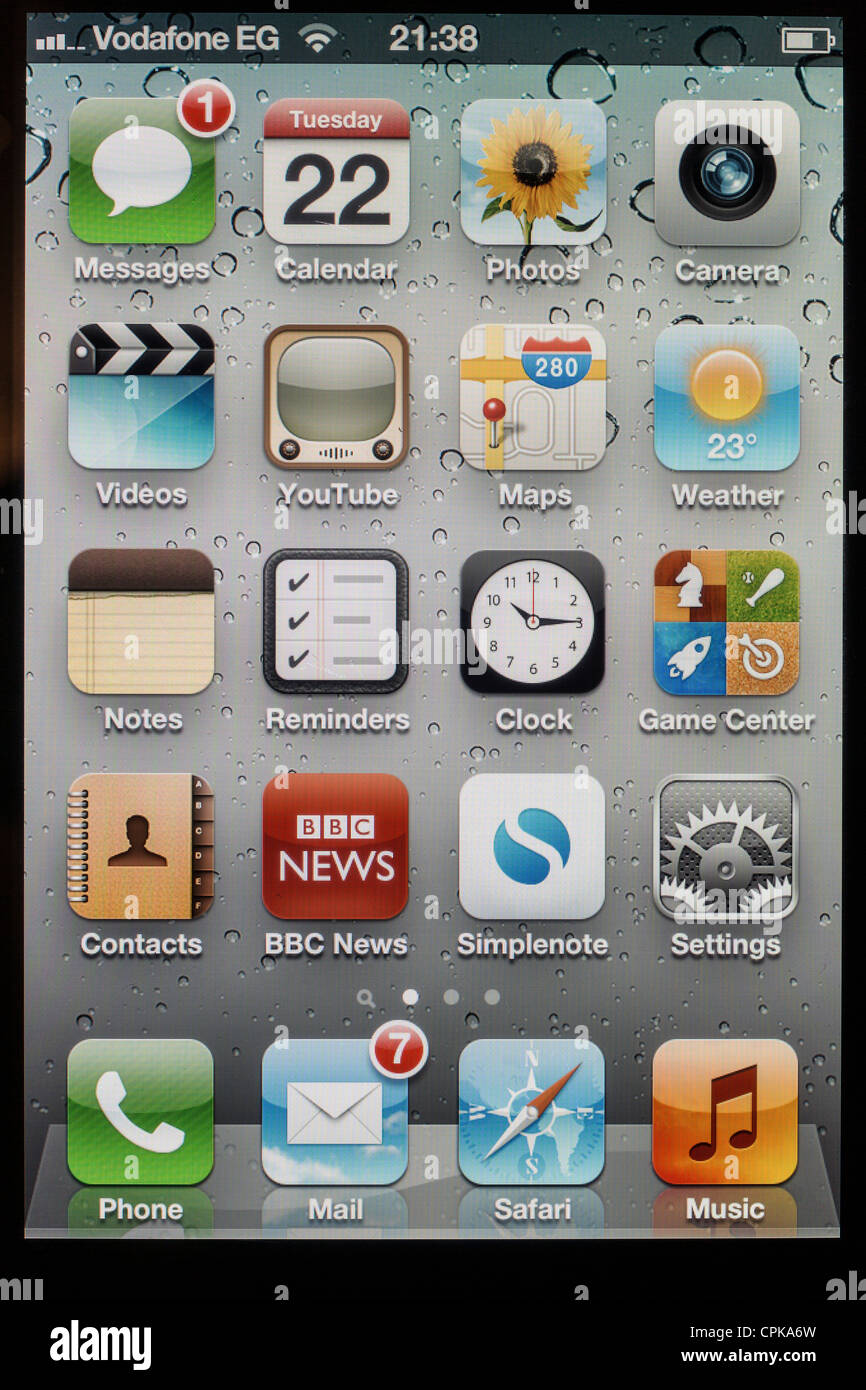 screen of Apple iPhone 4s showing applications on home page with new emails and new message - Stock Image