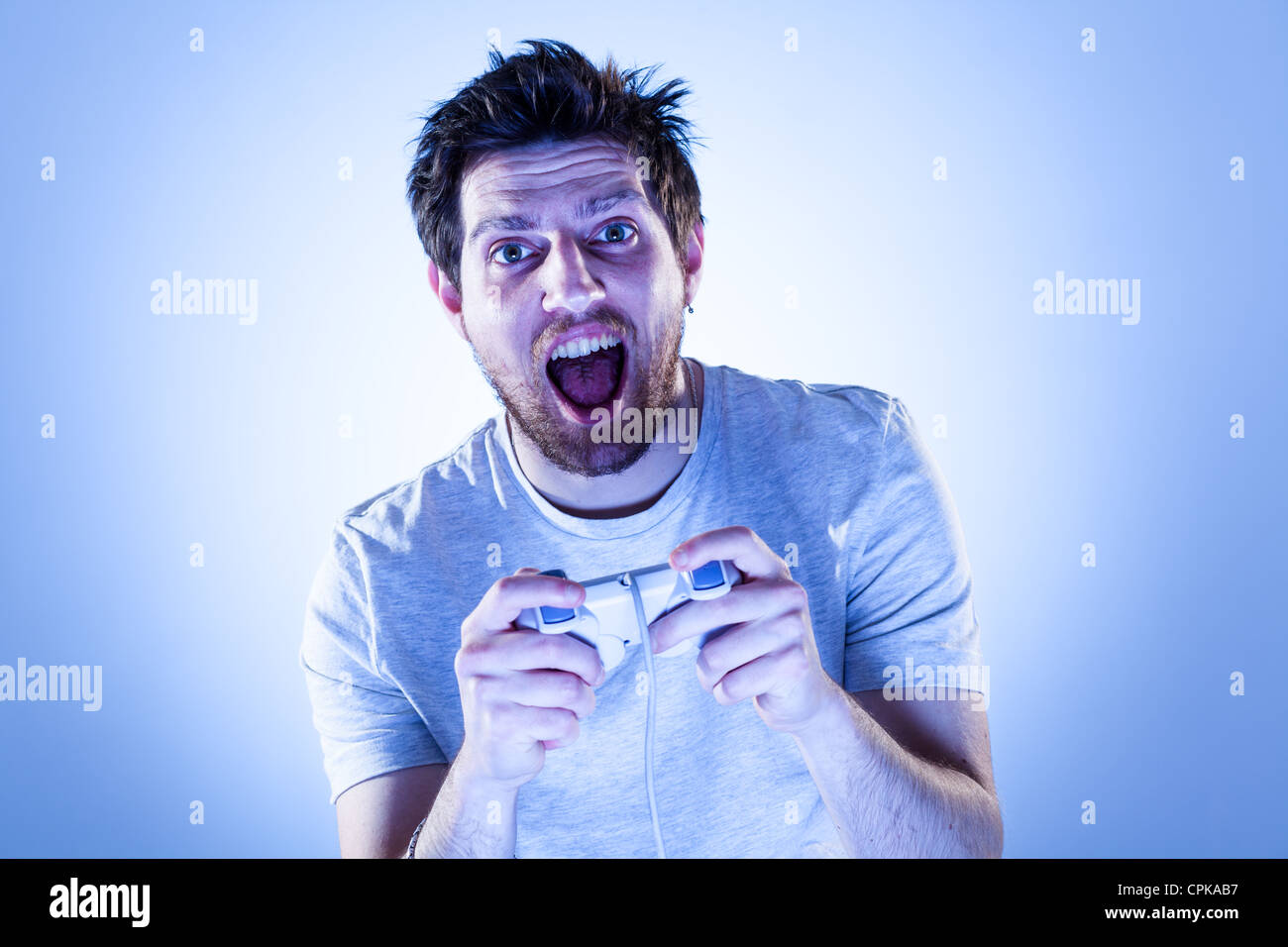Amazed Man Playing Videogames with Gamepad - Stock Image