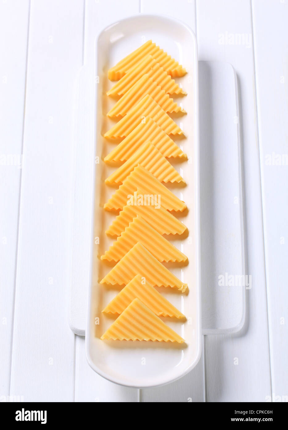 Hard cheese cut into triangles - Stock Image