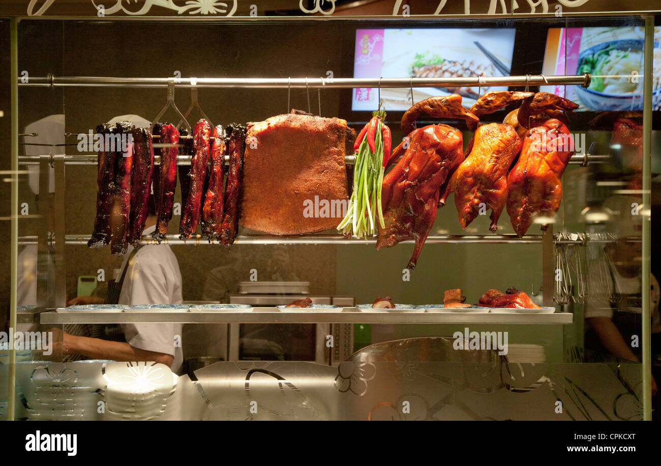 Chinese restaurant display window with barbecued meats, char sui pork, duck, sui yoke - Stock Image