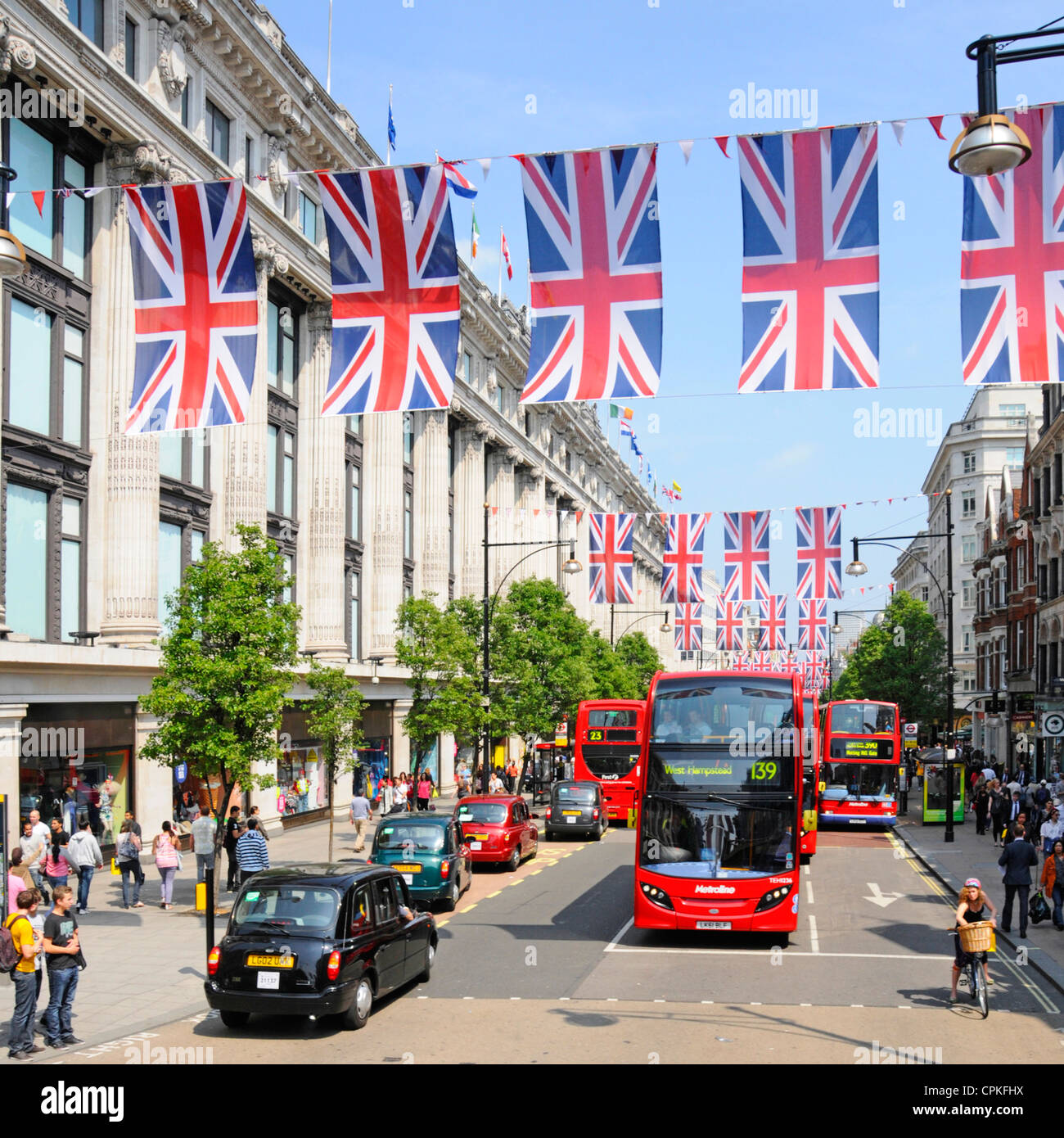 Black cab & buses in Oxford Street outside Selfridges with Jubilee Union Jacks which may also be in place during - Stock Image