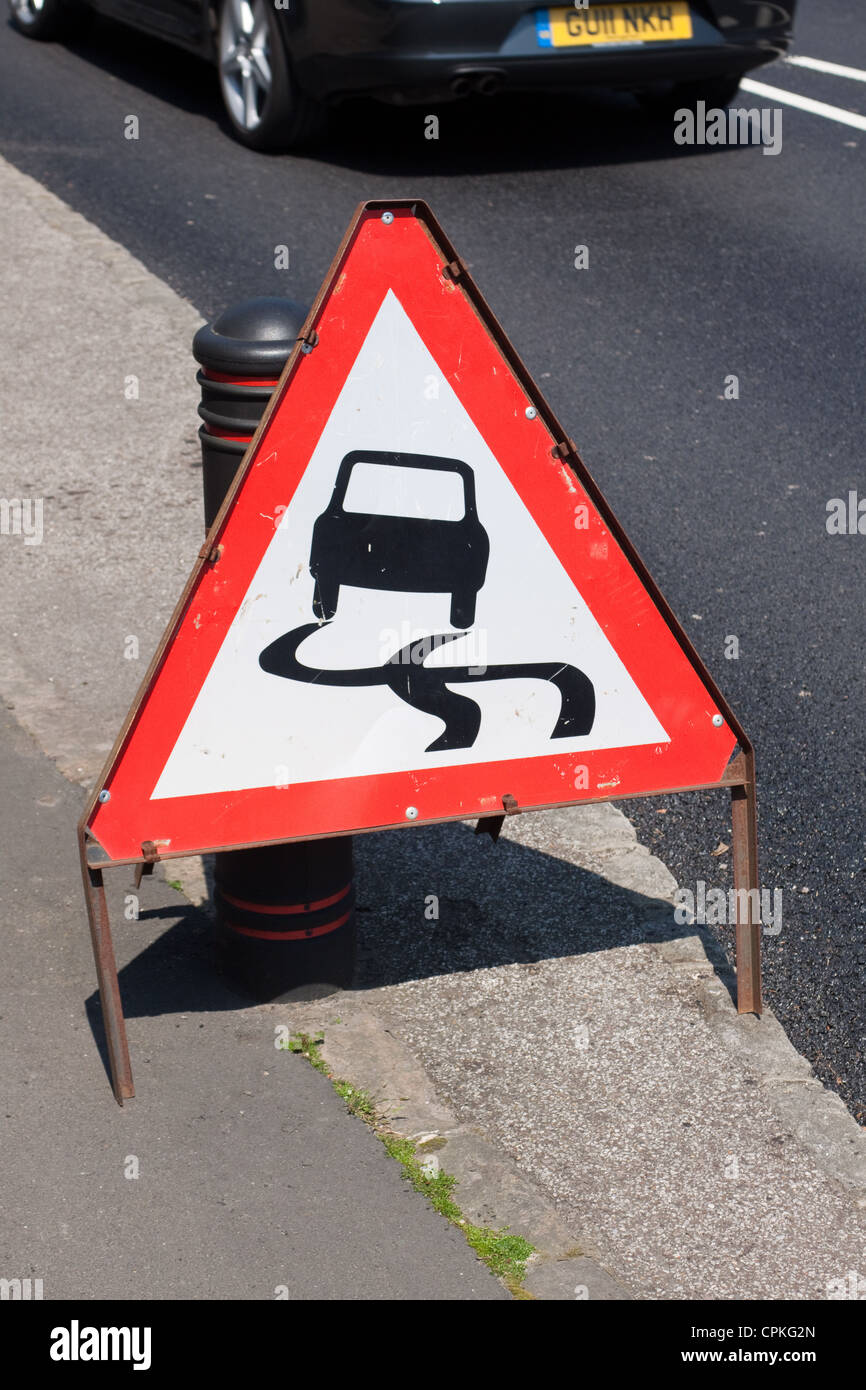 Slippery Road ahead warning traffic sign - Stock Image
