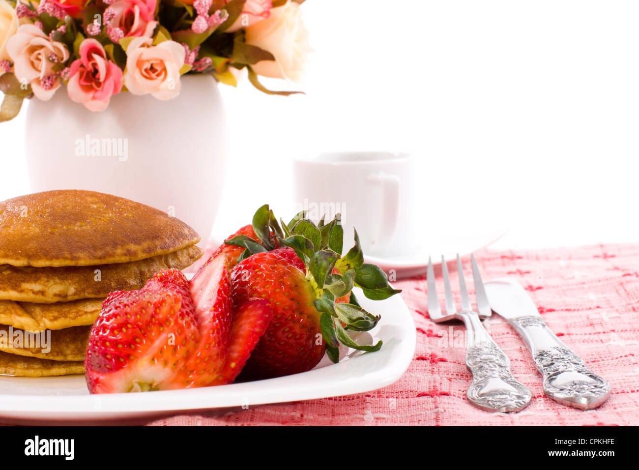Pancake and strawberry have maple syrup on top with coffee - Stock Image