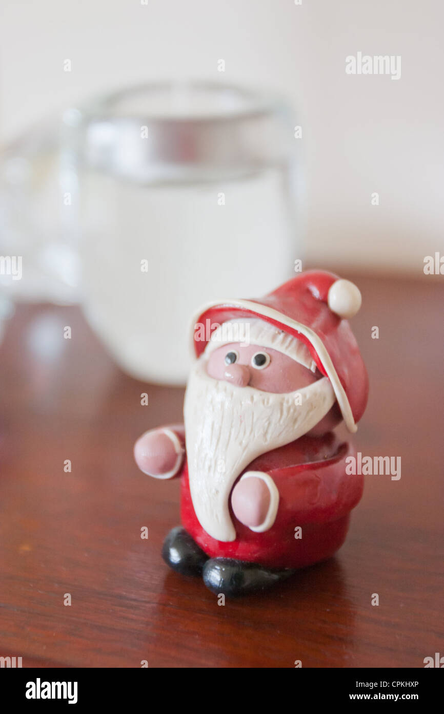 A christmas decoration of Santa Claus on a fireplace mantle in front of an unlit candle Stock Photo