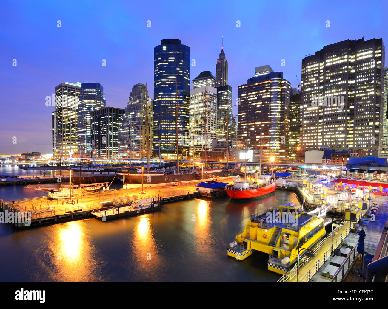 The historic district of South Street Seaport juxtaposed against the imposing Financial District skyscrapers. - Stock Image