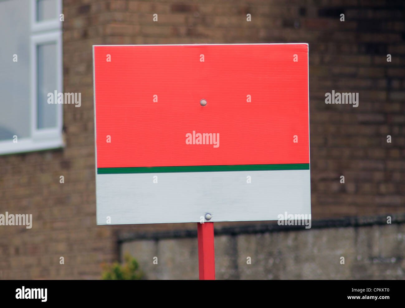 Blank for sale sign with copy space, house in background. - Stock Image