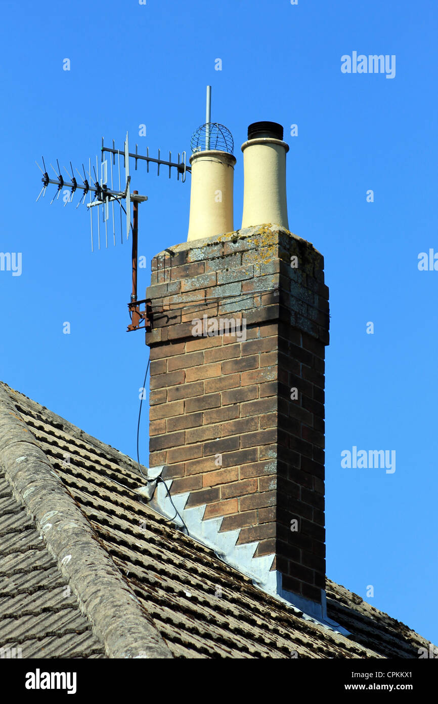 Chimney on tiled roof with aerial, blue sky background. - Stock Image