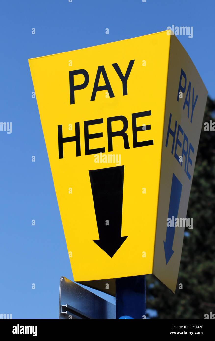 Yellow car parking pay here sign with blue sky background and directional arrow. - Stock Image